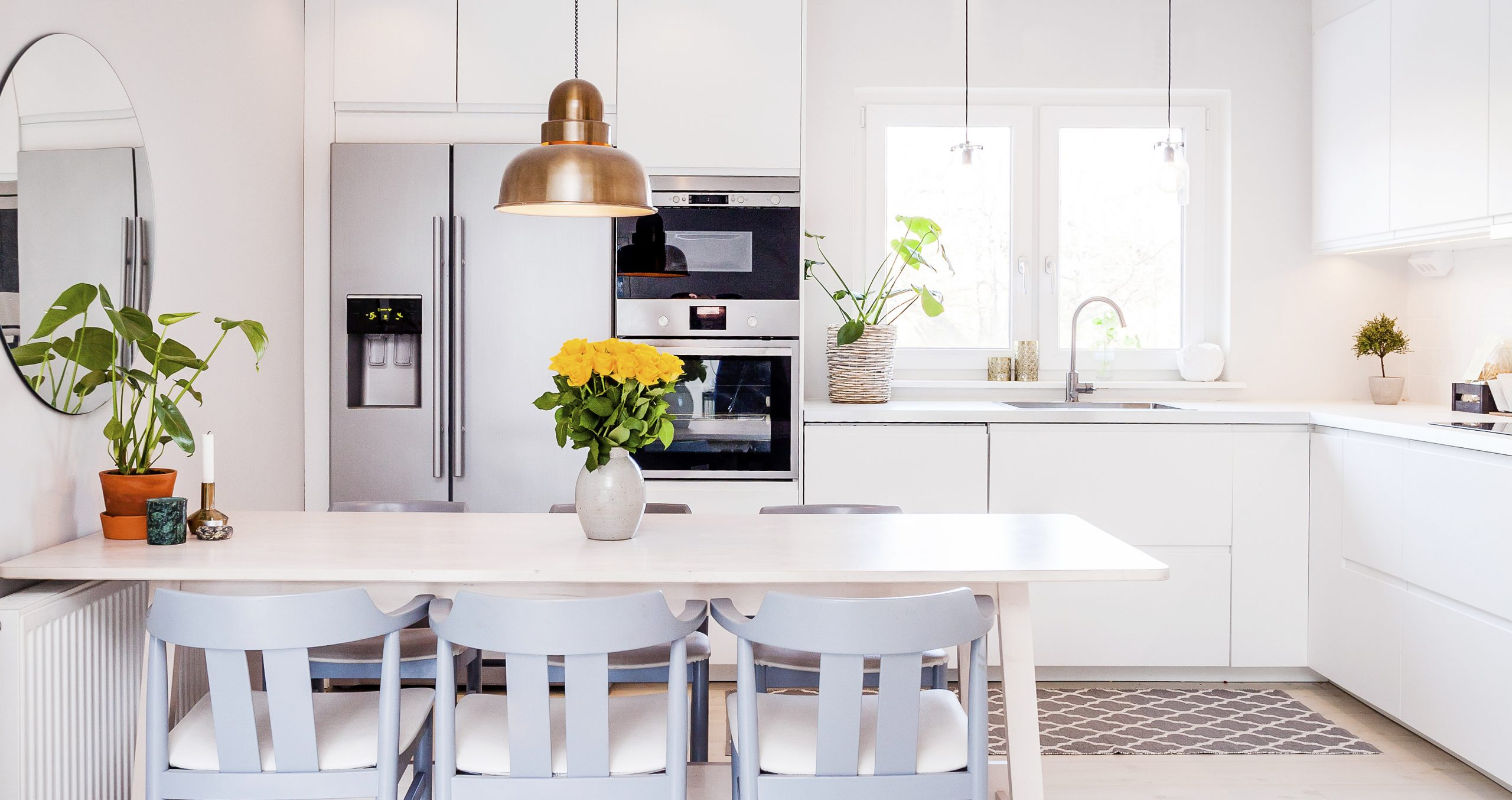 kitchen table with grey chairs in a white kitchen