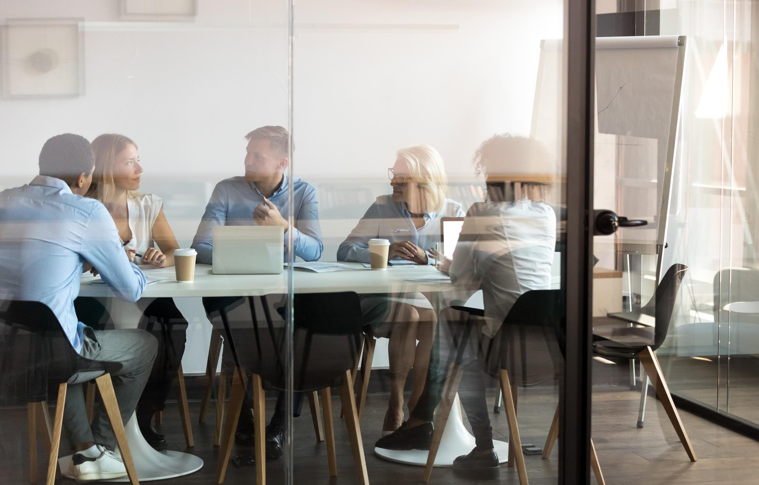 Business people negotiating at boardroom behind closed doors