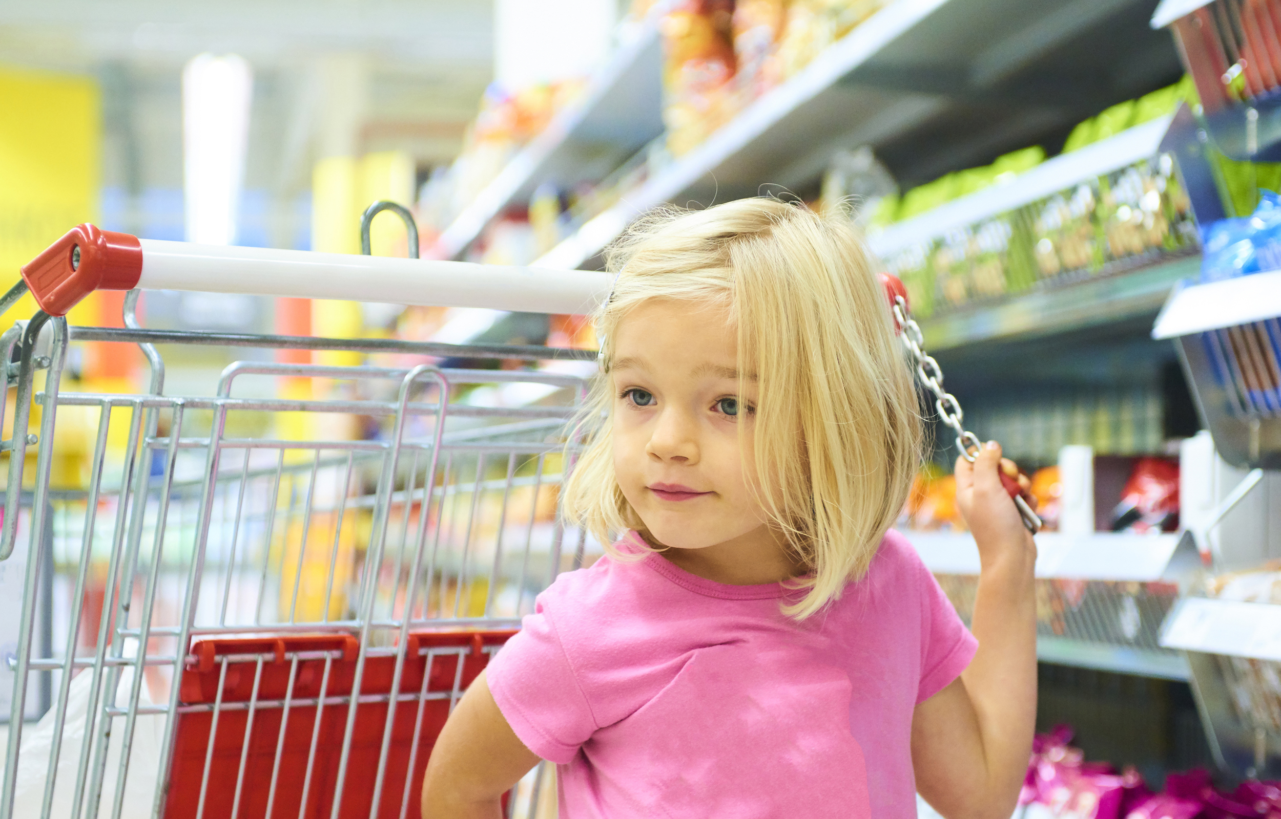 Little Child Blond Girl Shopping in the supermarket, pushing tro